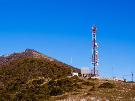 Red and white antenna tower on top of the mountain 写真素材 - 131702252