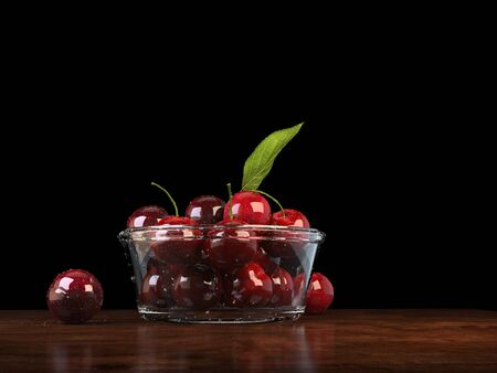 Fresh red cherries in a glass bowl on a wood tabletop