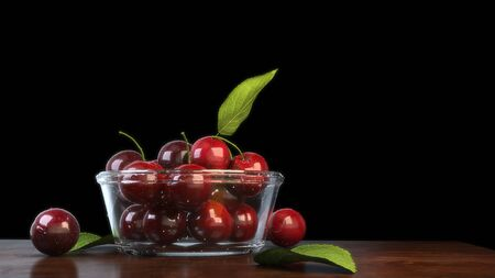 Glass bowl full of beautiful cherries on a polished wood table