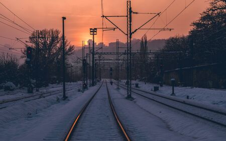 Snow covered empty train tracks at sunset Фото со стока