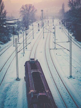 Train passing through the snow covered train tracks Фото со стока