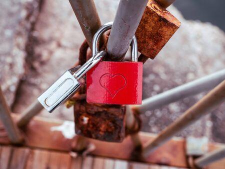 Red love lock with heart symbol, locked on a bridge rail