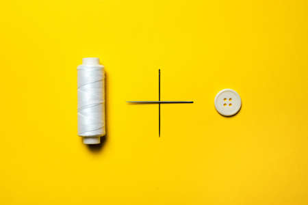 A spool of white thread, embroidery needles that form a plus sign and a white button lie in a row on a bright yellow background