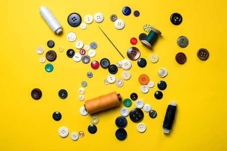 Sewing kit. Multicolored plastic buttons, spools of thread and sewing needles lie on a bright light yellow background