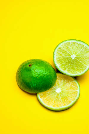 Fresh green lime wedges on bright yellow background