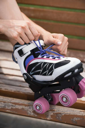 Mid adult woman sitting outdoors on a bench, tying roller skates. close up.