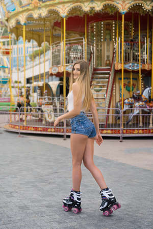 Woman roller skating in front of Colorful carousel in attraction park. 版權商用圖片 - 131843122