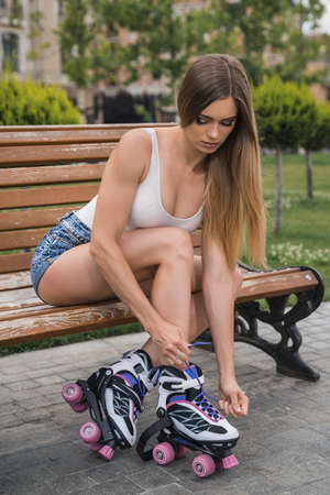 Mid adult woman sitting outdoors on a bench, tying roller skates Stockfoto