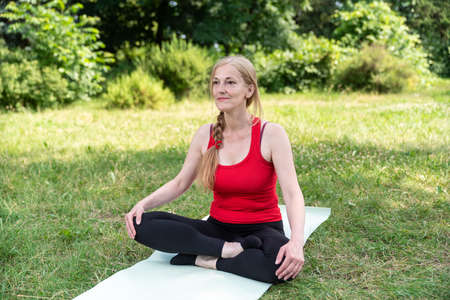 50 years old woman in red top relaxing and practice meditation outdoors.
