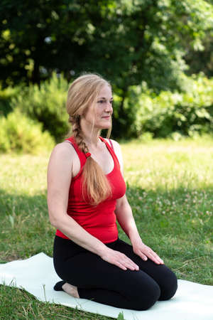 50 years old woman practice meditation outdoors in a park on a grass. Woman in red top Stok Fotoğraf