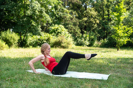 50 years old woman doing exercises in a park on a grass