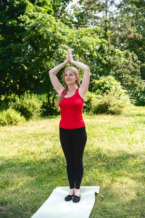 50 years old woman practice yoga on mat outdoors in a park on a grass. Woman in red top