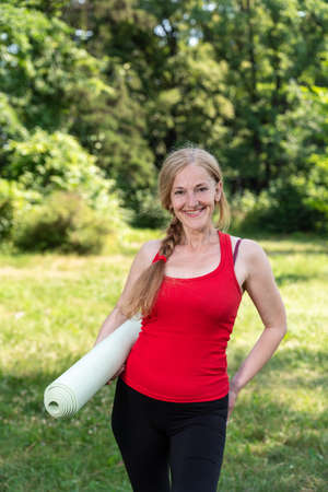 50 years old woman have a rest after the practice yoga outdoors in a park and holding mat. Woman in red top