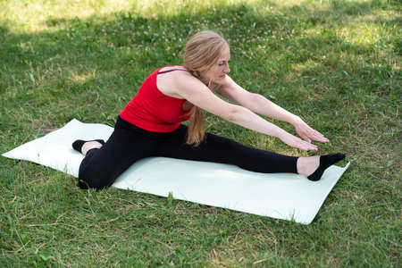 50 years old woman practice yoga on mat outdoors in a park on a grass.