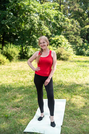 50 years old woman standing on a mat before stretching outdoors in a park on a grass.