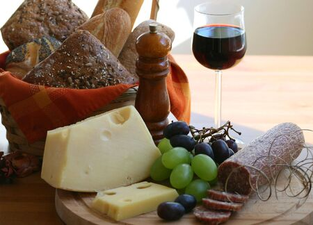 Cheese meat and wine in rustic still life photo