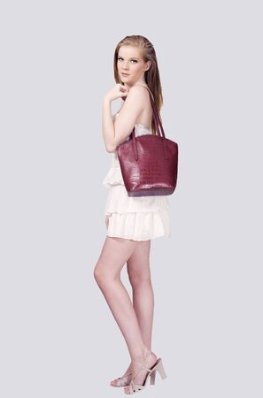 Young woman with red leather handbag photo