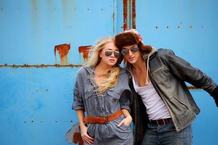 Attractive adventurous couple, with grunge wall background photo