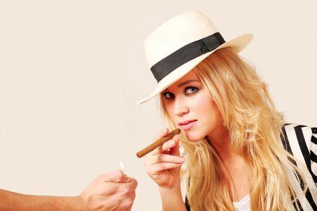 Stylish young woman lighting cigar