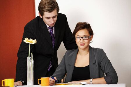 Attractive businesswoman with colleague in meeting or office photo