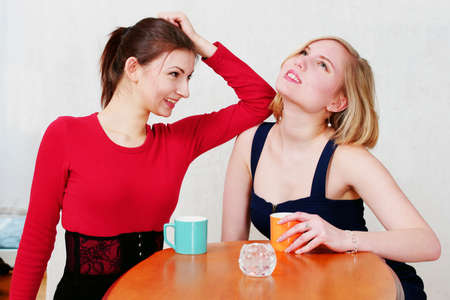Two pretty girls at coffee time chatting and laughing Stock Photo - 8804379