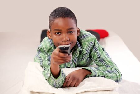 Cute boy with TV remote changing channel Stock Photo - 8989092