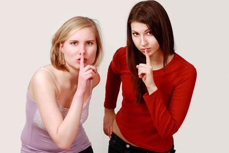 discreto: Dedo de las niñas en los labios en gesto silencioso o secreto