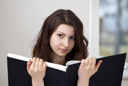 Intelligent studious girl with large book Stock Photo - 9124073