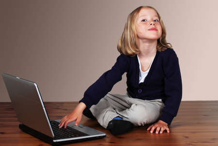 Child on laptop in playful mood photo