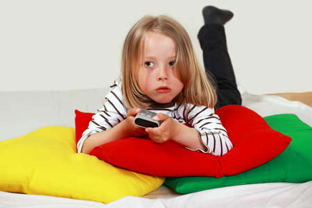 Cute child with TV remote changing channel