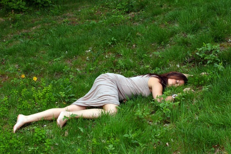 attacked: Womans body lying in grass field Stock Photo