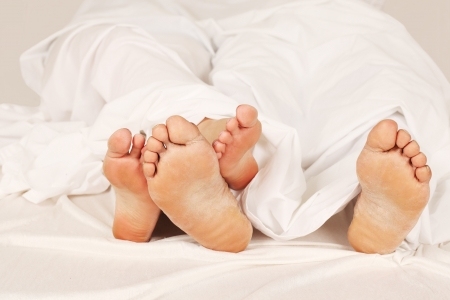 man feet: The feet of a couple in bed Stock Photo