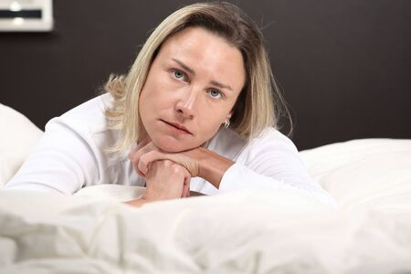 bedsheets: Beautiful woman thinking, horizontal face closeup with copy space