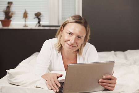 bedsheets: Beautiful woman with laptop working on bed