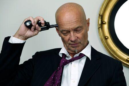 Desperate businessman puts gun to his head Stock Photo