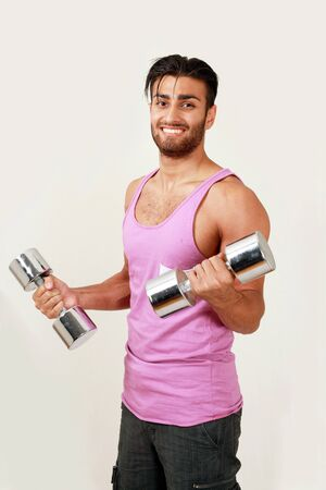 Smiling gym trainer with dumbbells photo