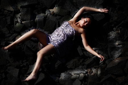 Woman on the rocks caught in lights photo