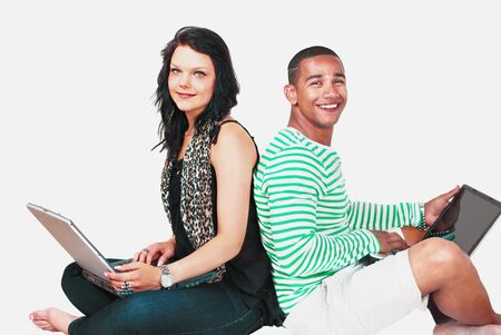Two attractive people on laptops photo