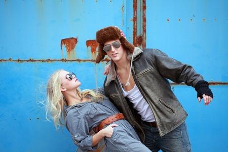 Urban couple swinging pose on grunge background photo