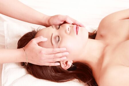 Hands massaging womans face in spa theme image photo