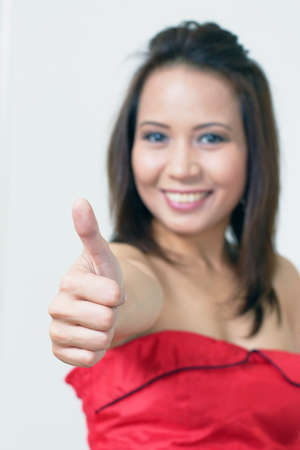 Thumbs up asian female with focus on hand Stock Photo - 10910565