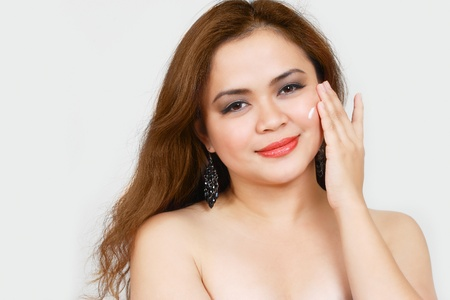 Young asian woman applying face cream photo