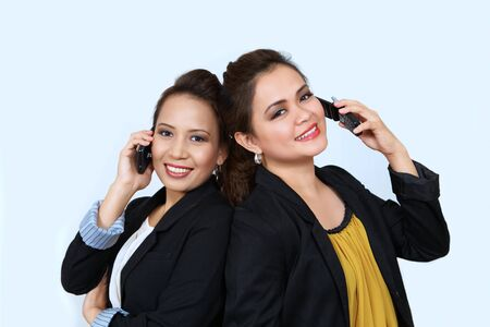 Two asian businesswomen on cell phones Stock Photo - 11141544