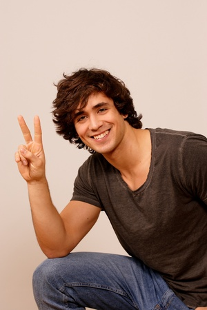 Peace sign - smiling handsome guy photo