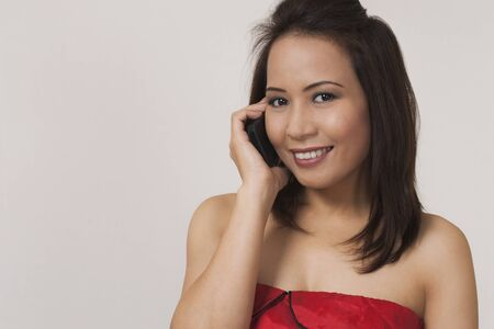 sincere girl: Smiling asian woman on cell phone