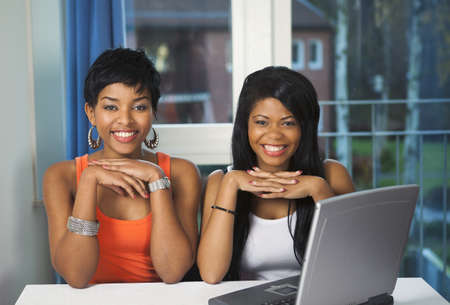 delighted: Happy girls viewing online service on laptop Stock Photo