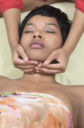 Young ethnic woman receiving reiki on neck position Stock Photo
