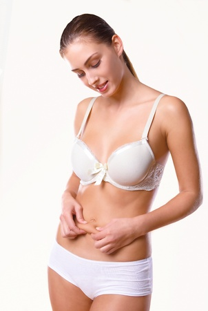 Young woman checking for abdomen cellulite Stock Photo - 11597284
