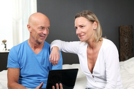 Adult couple at home discussing online services photo