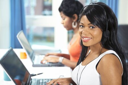office life: Smiling office worker with headset on computer station Stock Photo